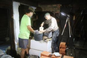 Muurarimestari Hardi Ojaste (oik.) ja ja amerikkalainen Richard Olsen tyhjentävät leivinuunin pohjaa kalkkikiven paloista ja savesta.