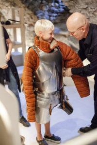 Haapsalun linnan näyttelyiden johtaja Jaak Mäll auttaa ritarivarustuksen nuoren museovieraan ylle.