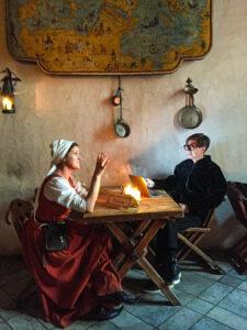 """Sykkö yllättyi Tallinnan Olde Hansa -ravintolassa. """"Mä en ole yhtään turistiravintolaihminen, mutta kun siellä on niin hirveän hyvä ruoka! Se oli kauhean kiva konsepti. Menen sinne uudestaankin"""", Sykkö kiittelee suosittua keskiaikaravintolaa, jossa hän on kuvassa työmatkalla."""